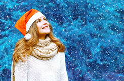 Christmas and people concept - happy woman in red hat Stock Photography