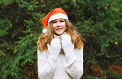 Christmas and people concept - happy young girl in winter hat Royalty Free Stock Photo