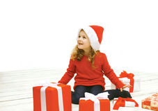 Christmas and people concept - joyful little girl in santa hat Royalty Free Stock Photography