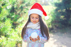 Christmas and people concept - little child in santa hat with snowball Royalty Free Stock Images