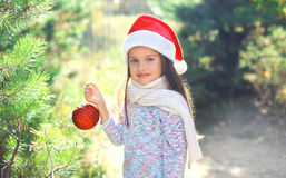 Christmas and people concept - little child in santa red hat with ball Stock Photo