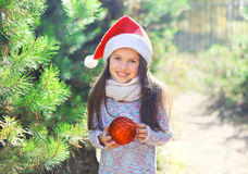 Christmas and people concept - little girl child in santa red hat with ball Royalty Free Stock Images