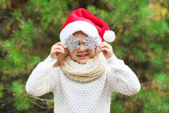 Christmas and people concept - little girl child in santa red hat with snowflakes Stock Photo