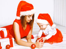 Christmas and people concept - mother and baby with gifts. On a white background royalty free stock images