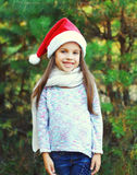 Christmas and people concept - smiling little girl child in santa red hat Royalty Free Stock Photo