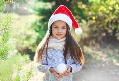 Christmas and people - little girl child in santa red hat with snowball Royalty Free Stock Image