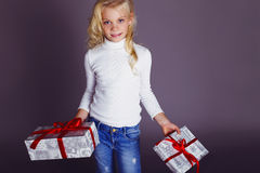 Christmas photo of cute little blond girl with presents. Cute little girl whith long blond hair and blue beautiful eyes holding Christmas presents Christmas Royalty Free Stock Photography