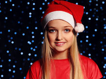 Christmas photo of cute little blond girl in santa hat and red dress Stock Photography