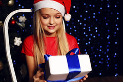 Christmas photo of cute little blond girl in santa hat and red dress holding a gift - box on the backgroud of holiday shining ligh Stock Photography