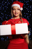 Christmas photo of cute little blond girl in santa hat and red dress holding a gift - box on the backgroud of holiday shining ligh. Cute little girl whith long Royalty Free Stock Image