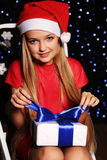 Christmas photo of cute little blond girl in santa hat and red dress holding a gift - box on the backgroud of holiday shining ligh. Cute little girl whith long Stock Image