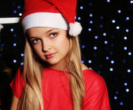 Christmas photo of cute little blond girl in santa hat and red dress holding a gift - box on the backgroud of holiday shining ligh Royalty Free Stock Photos