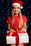 Christmas photo of cute little blond girl in santa hat and red dress holding a gift - box on the backgroud of holiday shining ligh Royalty Free Stock Image