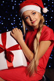 Christmas photo of cute little blond girl in santa hat and red dress holding a gift - box Stock Photo