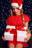Christmas photo of cute little blond girl in Santa hat and red dress holding a gift - box Royalty Free Stock Images