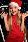 Christmas photo of cute little blond girl in Santa hat and red dress. Cute little girl with long blond hair and blue beautiful eyes in Santa hat and red suit Stock Photo