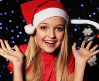 Christmas photo of cute little blond girl in Santa hat and red dress. Cute little girl with long blond hair and blue beautiful eyes in Santa hat and red suit Stock Images