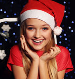 Christmas photo of cute little blond girl in santa hat and red dress. Cute little girl whith long blond hair and blue beautiful eyes in santa hat and red suit Stock Photos