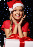Christmas photo of cute little blond girl in santa hat and red dress. Cute little girl whith long blond hair and blue beautiful eyes in santa hat and red suit Stock Photo