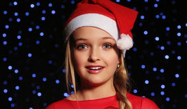 Christmas photo of cute little blond girl in santa hat and red dress. Cute little girl whith long blond hair and blue beautiful eyes in santa hat and red suit Stock Image