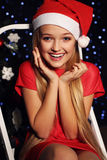 Christmas photo of cute little blond girl in santa hat and red dress. Cute little girl whith long blond hair and blue beautiful eyes in santa hat and red suit Royalty Free Stock Images