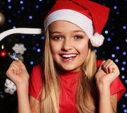 Christmas photo of cute little blond girl in santa hat and red dress. Cute little girl whith long blond hair and blue beautiful eyes in santa hat and red suit Royalty Free Stock Photography