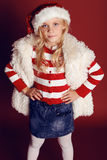 Christmas photo of cute little girl with long blond hair in Santa hat,fur coat smiling and posing in the studio Stock Photography