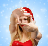 Christmas photo frame. Beautiful young woman in santa claus hat looking through creative photo frame on blue background with falling snowflakes Royalty Free Stock Photo