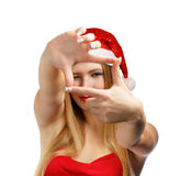 Christmas photo frame. Beautiful young woman in santa claus hat looking through creative photo frame isolated on white background Royalty Free Stock Photography