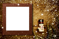 Christmas photo frame snowman card. Copyspace. Christmas photo frame background, cute snowman figurine with a gift on old wooden background glitter empty photo royalty free stock photo