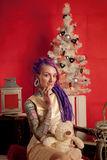 Christmas photo of a girl with purple dreadlocks and tattoos in the studio Royalty Free Stock Photo