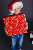 Christmas photo of  little boy in santa hat and jeans smiling with  Christmas gift. Holiday photo with  little boy in santa hat and jeans and a white sweater Royalty Free Stock Images