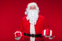 Christmas. Photo Santa Claus giving xmas present and looking at camera, on a red background Royalty Free Stock Photos