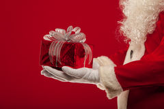 Christmas Photo of Santa Claus gloved hand with giftbox, on a red backgro Royalty Free Stock Image