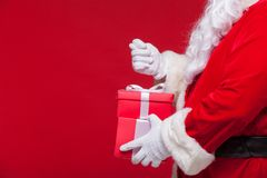 Christmas Photo of Santa Claus gloved hand with red giftbox. no fig Royalty Free Stock Photos