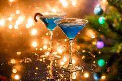 Christmas photo of two wine glasses with blue cocktail and garland Royalty Free Stock Photos