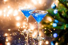 Christmas photo of two wine glasses with blue cocktail and garland Royalty Free Stock Photography