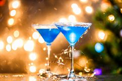 Christmas photo of two wine glasses with blue cocktail and garland Stock Image