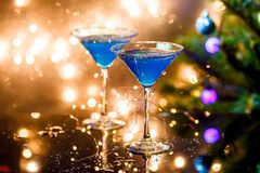 Christmas photo of two wine glasses with blue cocktail and garland Royalty Free Stock Images