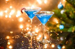 Christmas photo of two wine glasses with blue cocktail and garland. On blurred blue New Year`s background Stock Images