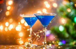 Christmas photo of two wine glasses with blue cocktail and garland Stock Images