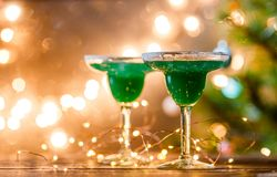 Christmas photo of two wine glasses with green cocktail Royalty Free Stock Photos