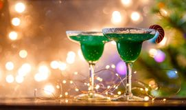 Christmas photo of two wine glasses with green cocktail. And garland on blurred blue New Year`s background Stock Images
