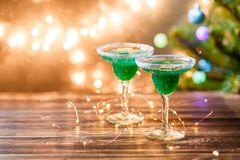 Christmas photo of two wine glasses with green cocktail Stock Photo