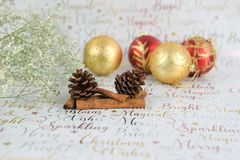 Christmas photography of flowers with glitter pine cones and baubles on xmas wrapping paper background stock images