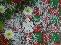 Christmas photography image with flowers and tree decoration of angel and heart with holly and red berries sprinkled with snow. Studio photograph with red green Royalty Free Stock Photos