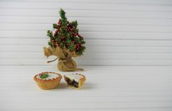 Christmas photography image of christmas food mince pies and mini toy tree with natural white wood background Royalty Free Stock Image