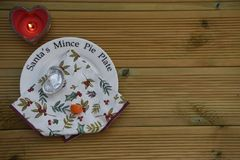 Christmas photography image of Santa mince pie plate showing eaten carrot from reindeer and empty plate with heart lit candle Stock Images