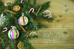Free Christmas Photography Image With Green Tree Branch Leaves Cinnamon Orange Slices And Colorful Bauble Decorations And Snow Stock Photo - 103932550