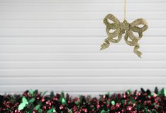 Christmas photography image of xmas decoration hanging up gold glitter bow bauble with tinsel and white wood background Royalty Free Stock Images